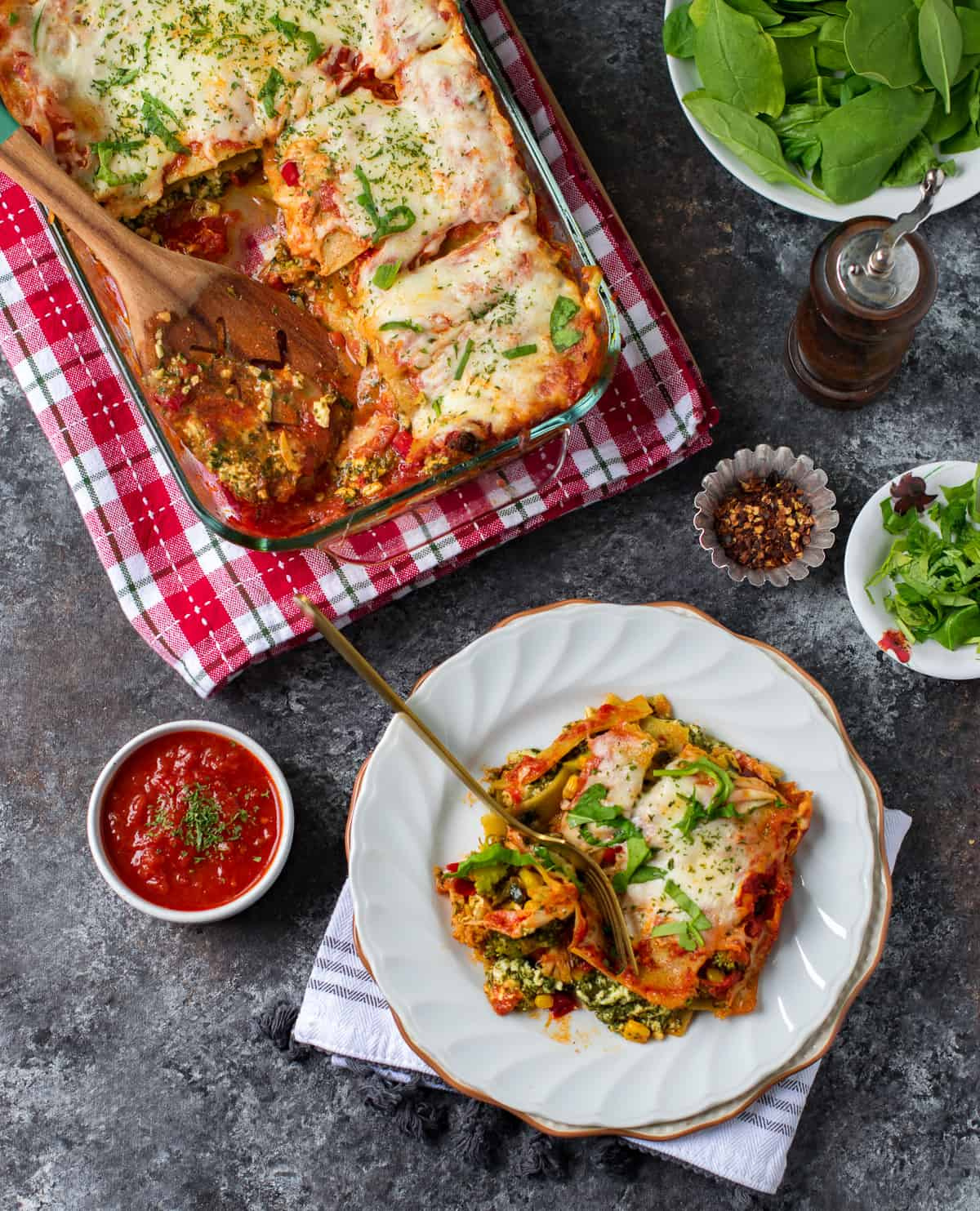 Veg lasagna served on a plate with some pasta sauce on the side