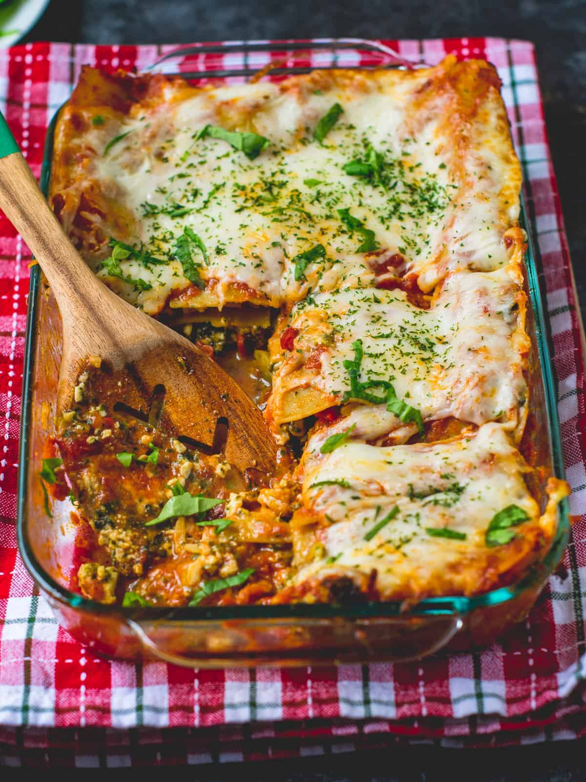 Veggie lasagna in a baking pan with a serving spoon