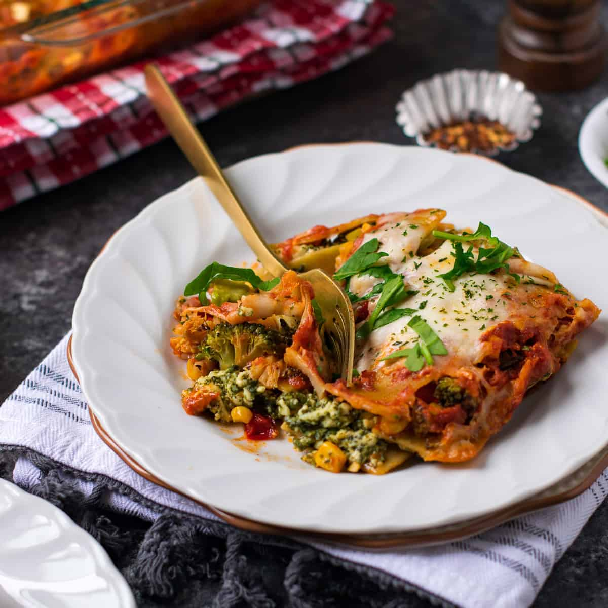 Veg lasagna served on a white plate with a fork