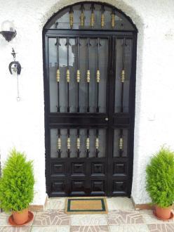 puerta de entrada a casa rural flanqueada por macetas con pinos