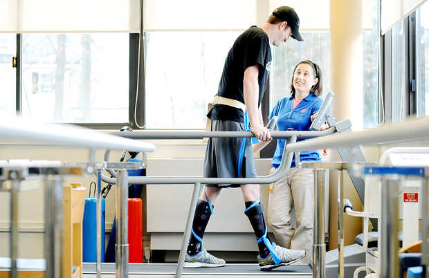"Nate Clark of Dixfield works with his physical therapist, Sophie Herr, at the New England Rehabilitation Hospital of Portland. Clark suffered a spinal cord injury during a snowmobile hill climb race at Black Mountain ski area on Jan. 11. He is able to use his legs, but not nearly to the extent that he could before the accident. ""Nate has to teach his brain to use his legs in a different way,"" Herr said. Clark has physical therapy once a week."