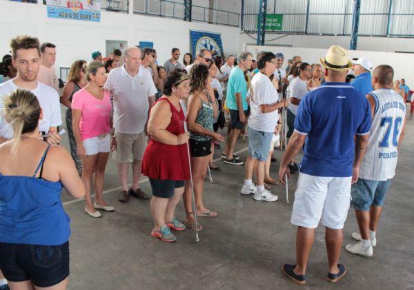 A imagem na horizontal mostra o ensaio da escola de samba Águia de Ouro com a ala para deficientes visuais. Dezenas de pessoas estão na quadra da escola de samba, um local amplo e iluminado com paredes brancas. Fim da descrição.