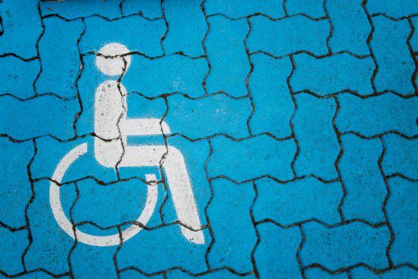 A imagem está no formato retangular na horizontal. Nela contém o símbolo da pessoa com deficiência na cor branca em cima de um asfalto na cor azul. Fim da descrição.