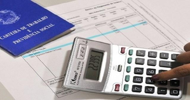Uma calculadora e uma carteira de trabalho sobre uma planilha financeira