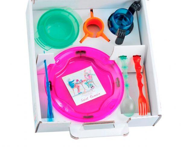 A imagem está no formato retangular na horizontal. Nela contém um kit O kit Suitye Easyeat com talheres, suportes antiderrapantes e prato com tampa e borda de segurança. Fim da descrição.
