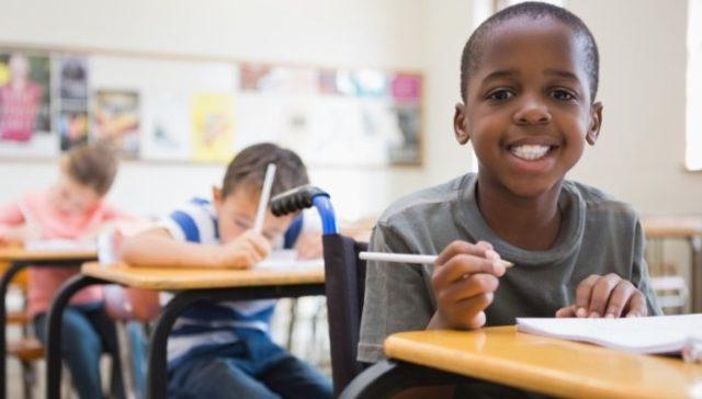 Descrição da imagem #PraCegoVer: Imagem no formato retangular, na horizontal. Uma sala de aula, com três alunos, sentados em suas carteiras. Em primeiro plano, vemos um aluno cadeirante. Os alunos estão realizando uma atividade. O aluno em evidência segura um lápis com a mão direita, enquanto apoia a mão esquerda em um caderno, que está em cima da mesa. O menino cadeirante é negro, tem cabelos curtos e usa uma camiseta na cor cinza. Ele está sorrindo e olhando para a câmera. e Fim da descrição.