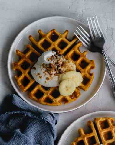 pumpkin waffle on a plate with whipped cream, bananas, pecans and pumpkin pie spice
