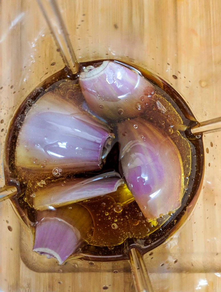 Shallots, olive oil, honey, and red wine vinegar in a nutribullet glass