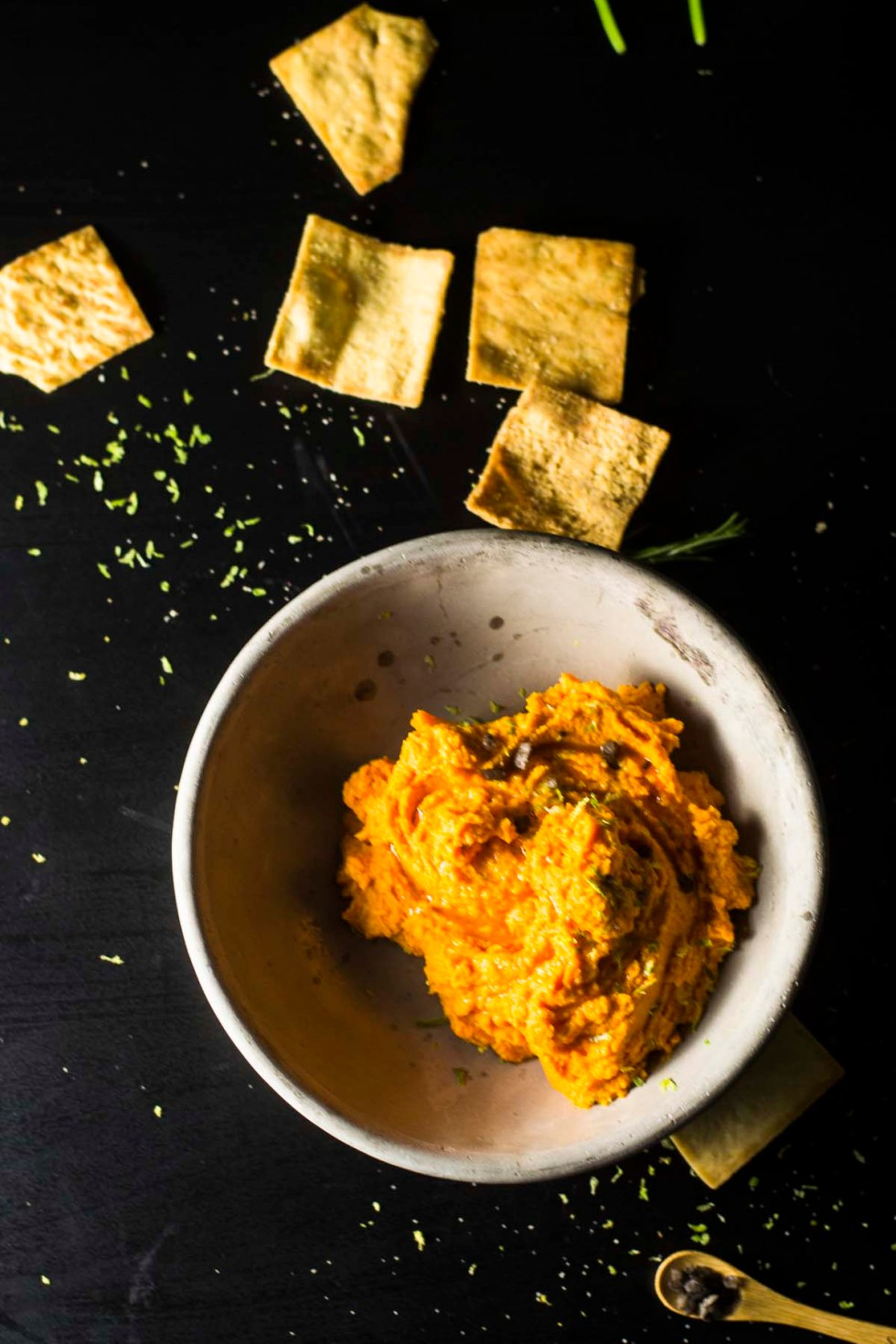 Carrot hummus in bowl with spoon and pita chips on table