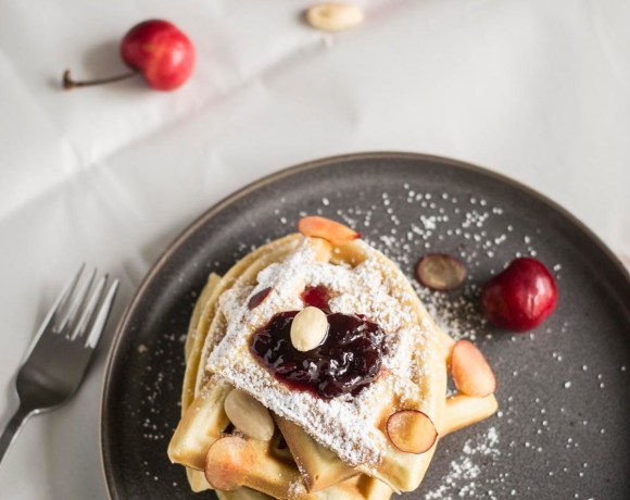 Easy Breakfast Waffles with Cherry Marmalade on a plate with cherries on a table