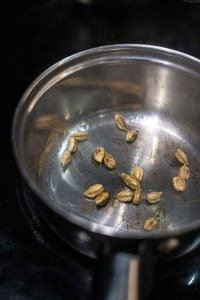 Cardamom pods cracked and toasting in a pot with olive oil