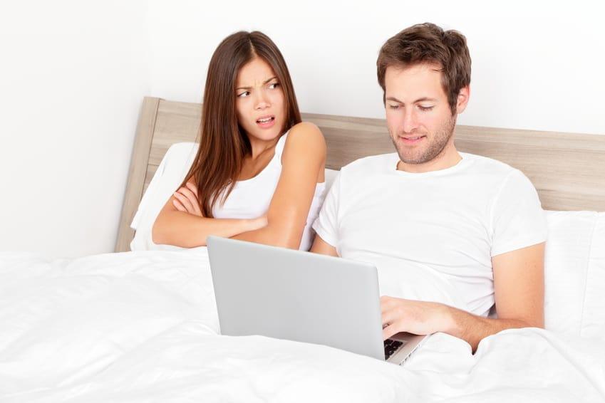 Frau mit angewidertem Gesichtsausdruck und Mann mit Laptop im Bett