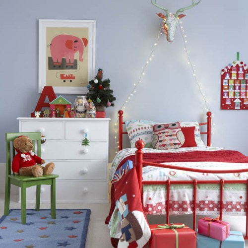 Childrens colour coordinated bedroom decorated in a festive theme. Fairy lights, stocking hanging from bedstead, presents wrapped in a variety of colours, single bed with red and white bedding, advent calendar, miniature christmas tree, plastic animal mount, IH Not Used 01/2012