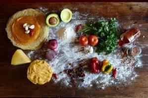 Diversos ingredientes sobre mesa: Chilli, guacamole, abacate, avocado, tortilla, fubá de moinho d'água, pimentões, pimentas, tomate, coentro, queijo parmesão