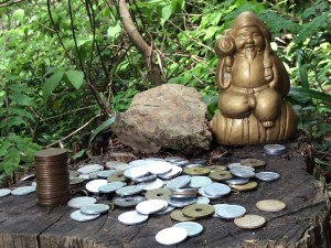 A small Buddha statue with several offerings on the Koburi Pass hiking trail