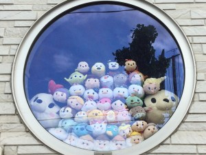A window in a home near the park proudly displaying its winnings from the UFO Catcher games