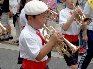A young trumpeter working hard on a humid day