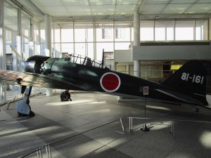 "A Japanese ""Zero"" fighter plane, similar to the ones used in the 1941 attack on Pearl Harbor, is displayed in the lobby of the Yūshūkan military museum"