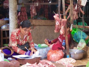 A butcher catches up on paperwork as her raw product hangs all around her.