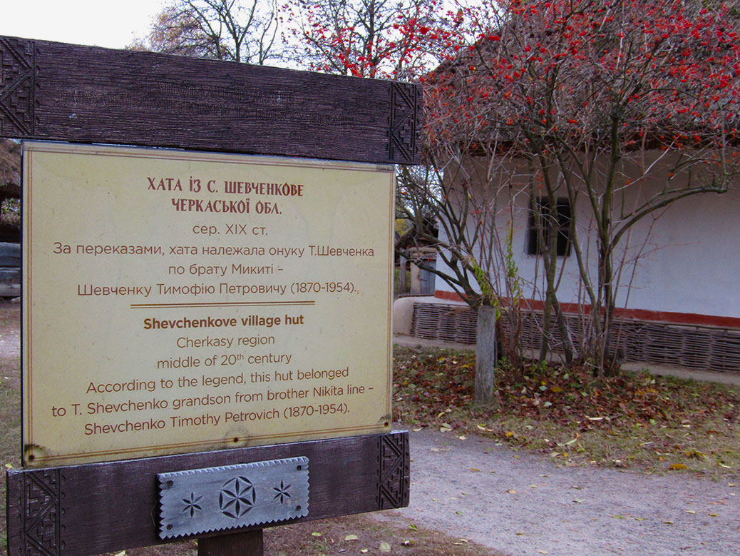 A sign explaining the origins of the home. The home and a kalyna tree are in the background.