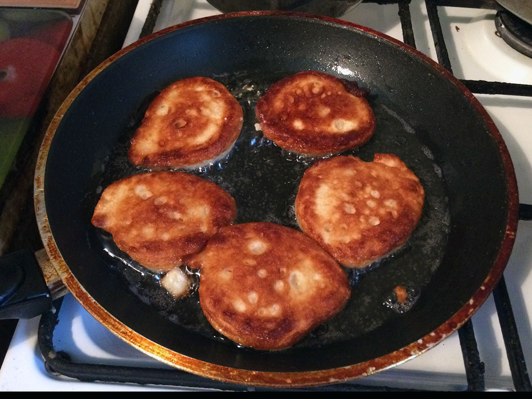 Oladi pancakes browning in the pan; my aunt is not afraid of oil!