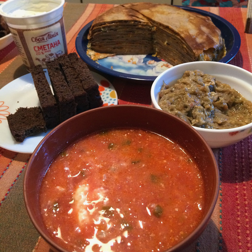 Red beet borscht soup with an eggplant dip and a layered crepe dish.