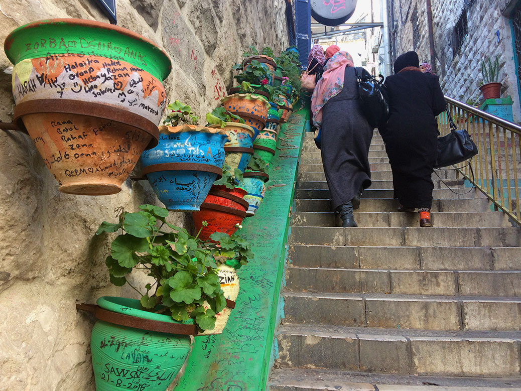 A staircase off Prince Muhammad Street features colorful flowerpots with graffiti left by visitors from around the world.