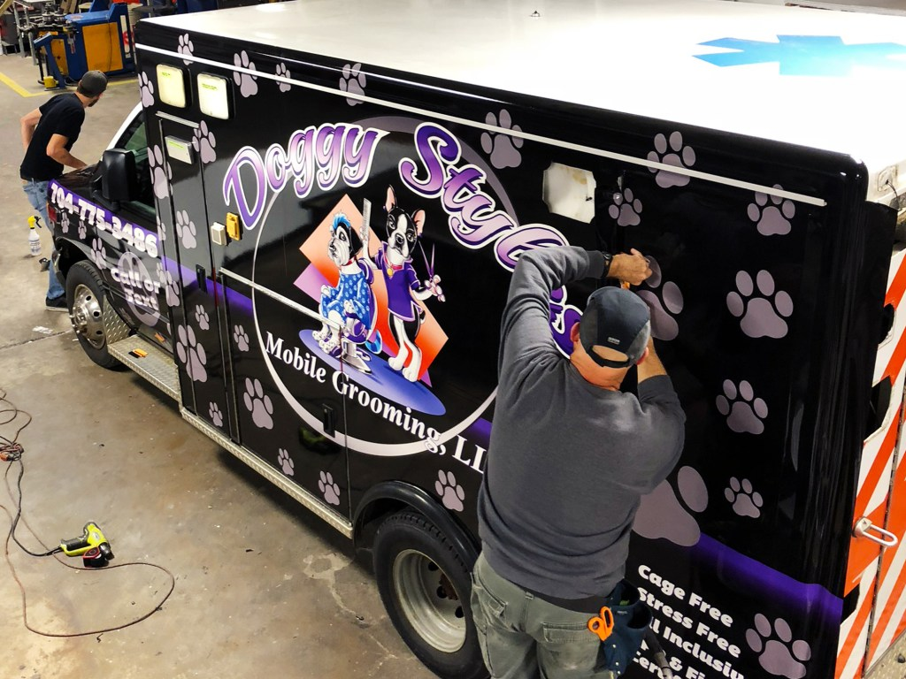 Vinyl graphics installers applying a wrap to an ambulance.