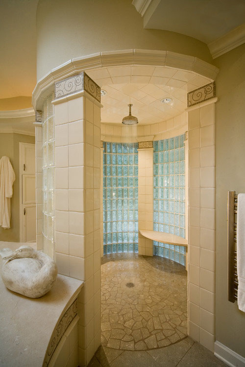 this custom luxury shower room by deep river partners makes great use of the open space in the center of a larger bathroom the tile columns glass tile