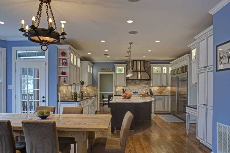 neutral colored renovated kitchen flows into dining room with blue walls