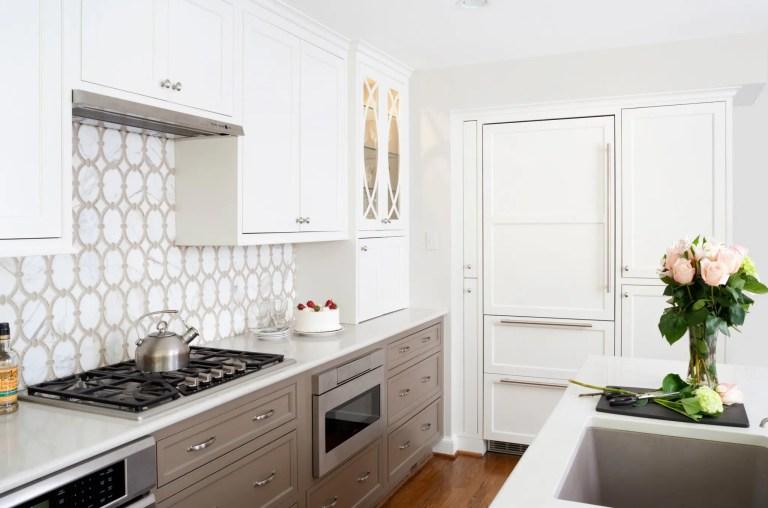 traditional kitchen neutral color palette gray toned lower cabinetry paneled refrigerator geometric tile backsplash gas stovetop range