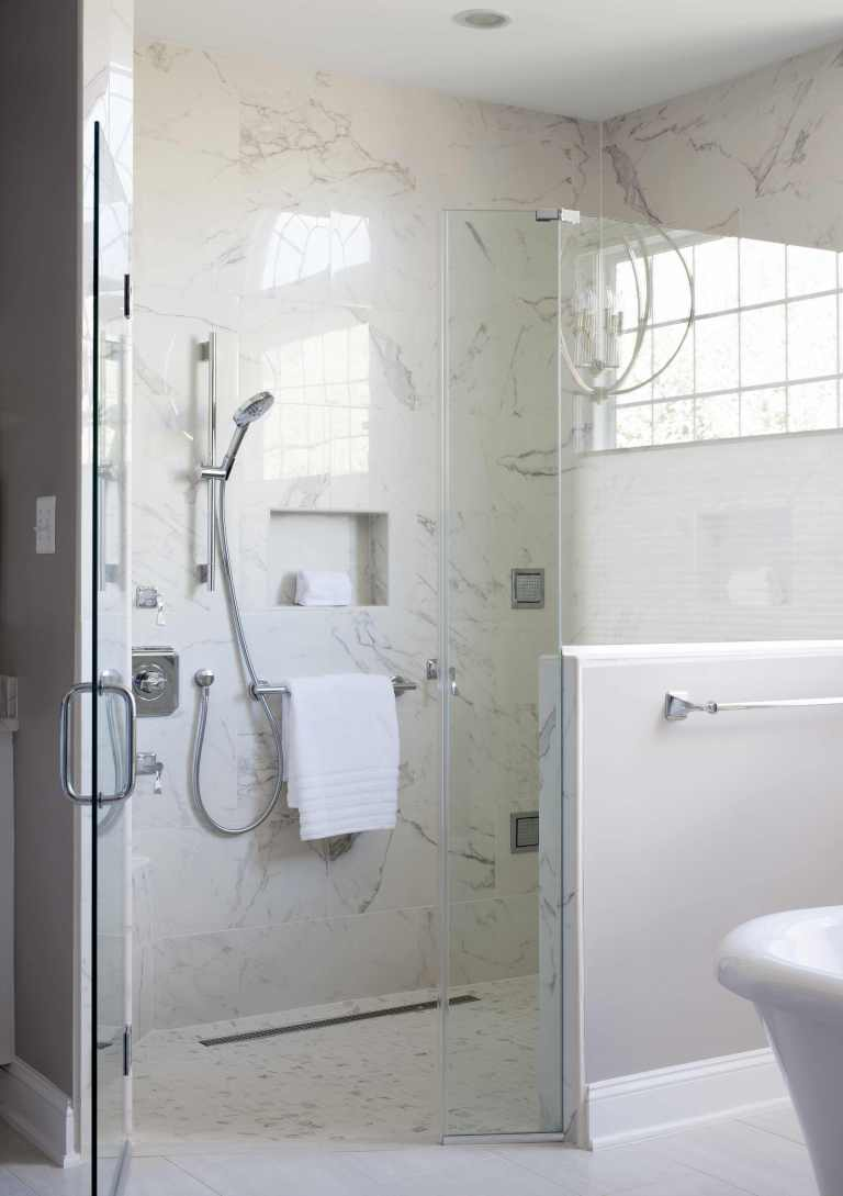 large separate shower stall with half glass wall built in storage nook neutral color palette