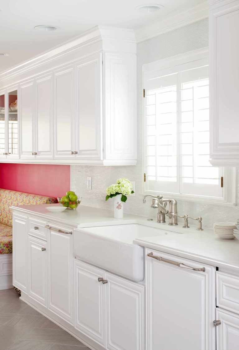 renovated kitchen with white cabinetry and farmhouse sink hot pink wall