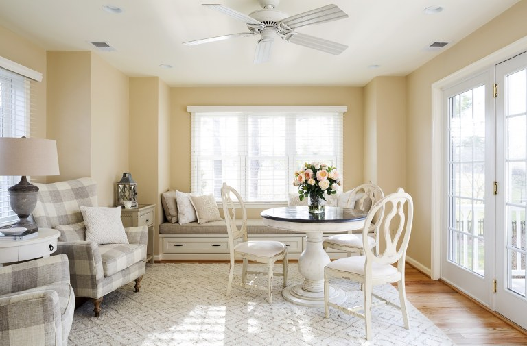 bright living area large window yellow color palette window seat and french doors