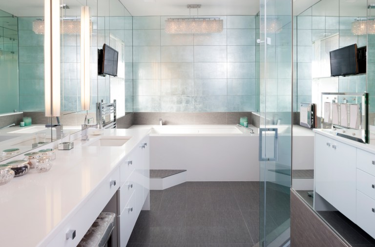 modern bathroom mirror wall vanity with white cabinets reflective tiles over bathtub