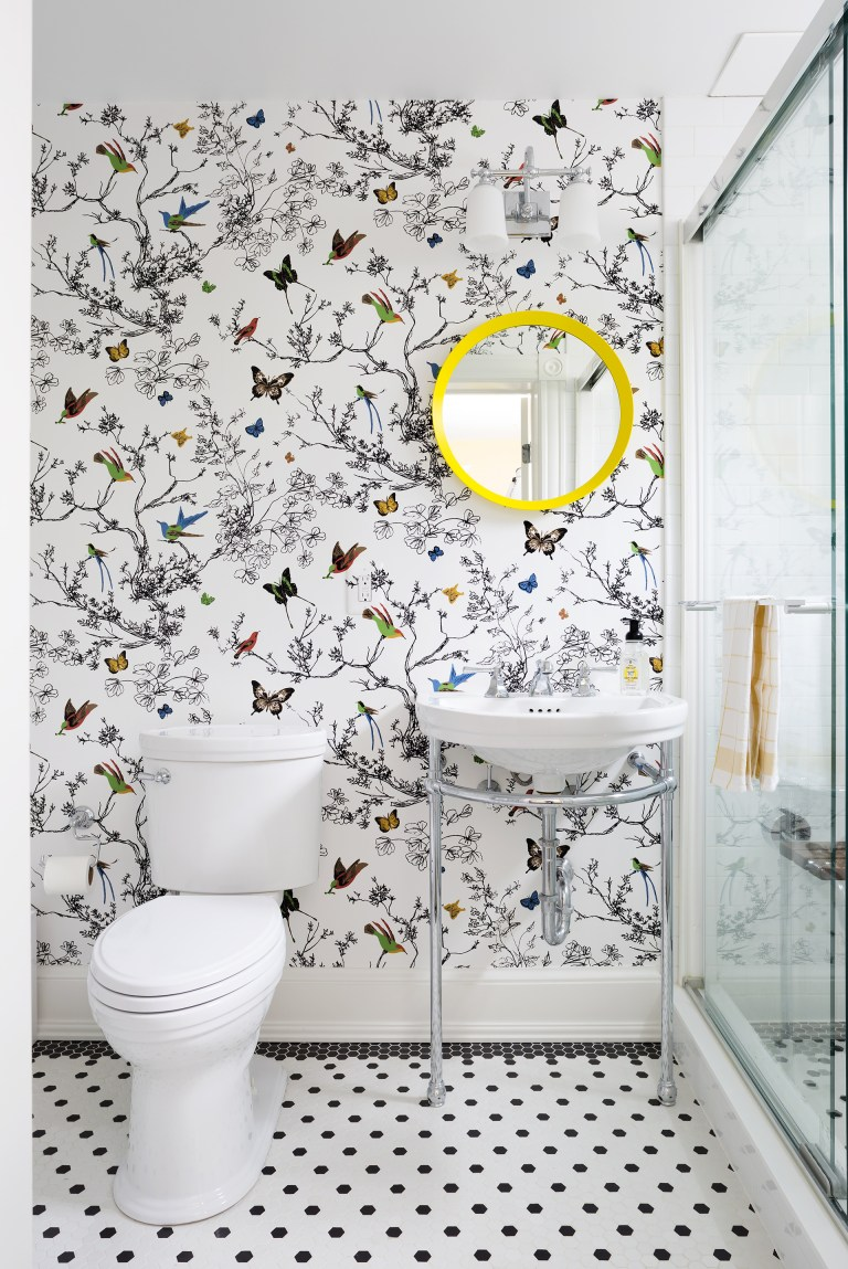 bright bathroom with butterfly wallpaper glass door shower sink with exposed pipes black and white floor