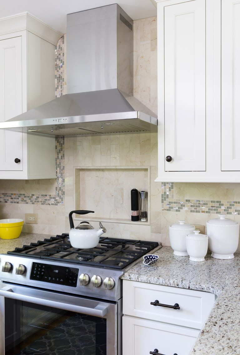 stainless steel gas range and hood with nook built into backsplash