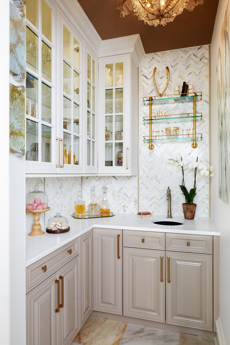 kitchen with gray lower cabinetry white upper cabinetry with glass doors bronze ceiling bronze and gold fixtures and hardware open glass shelving