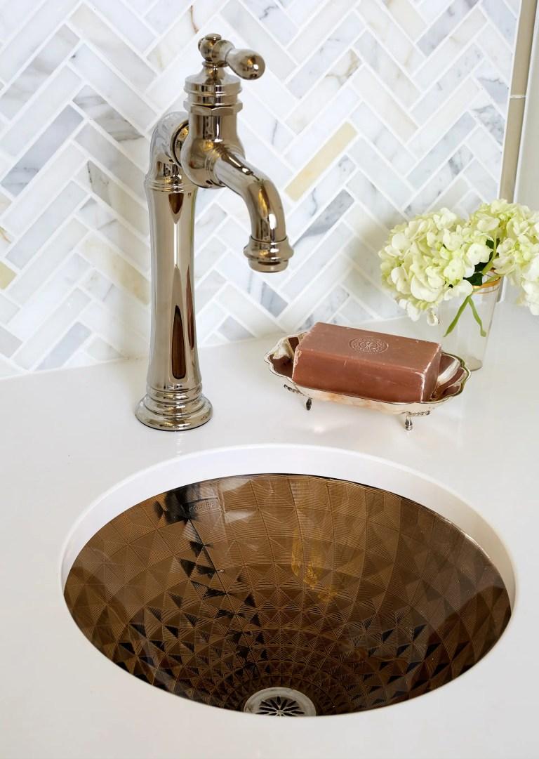 bronze mini kitchen sink with bronze fixtures chevron tile backsplash