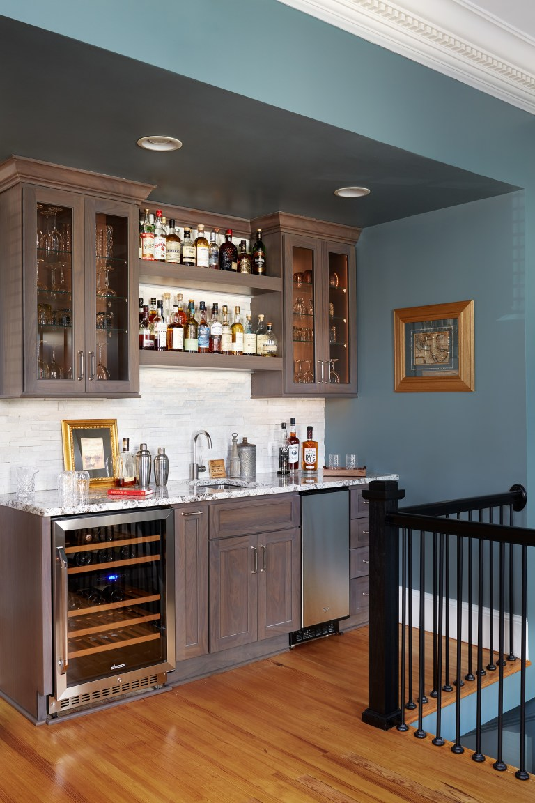 indoor bar area stainless steel mini refrigerators open shelving and upper cabinets with glass doors blue walls