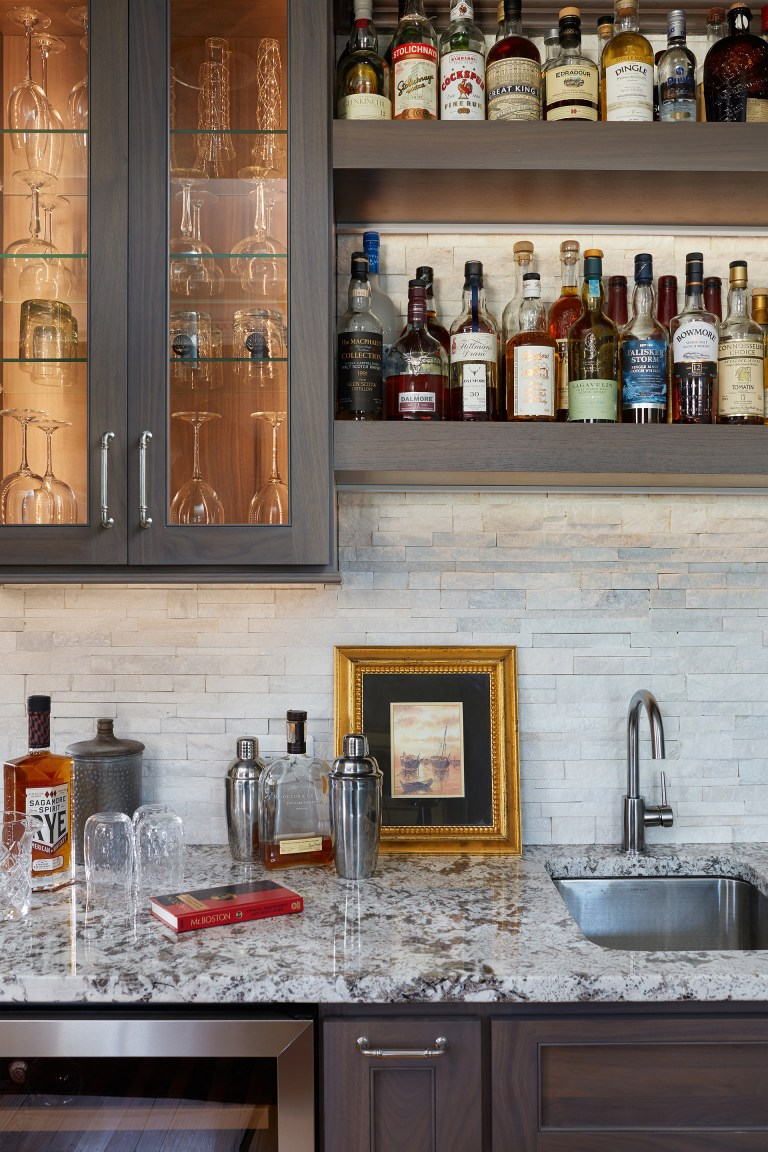 minibar area with mini refrigerator bar sink open shelving upper cabinets with glass doors tile backsplash