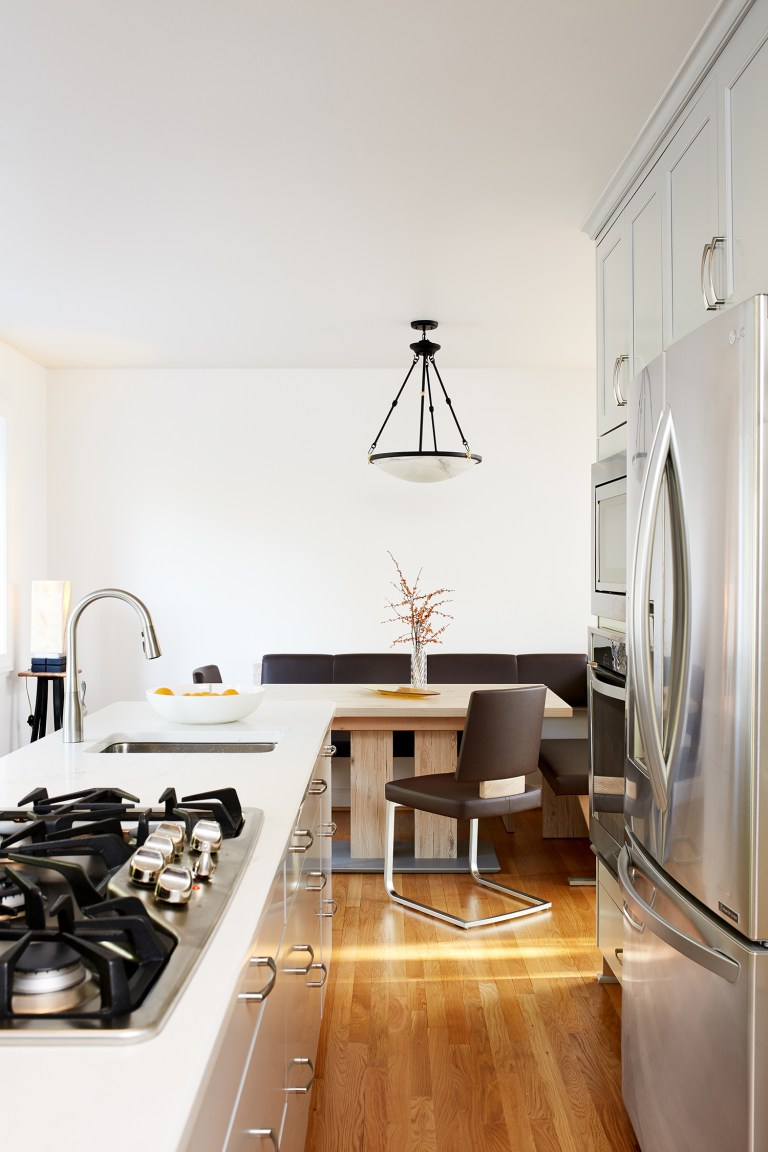kitchen open to dining area white cabinetry stainless steel appliances and gas stovetop wood floors