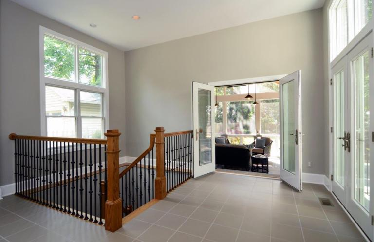 staircase up to hallway with double glass doors to living area and outdoor space large window tile floors