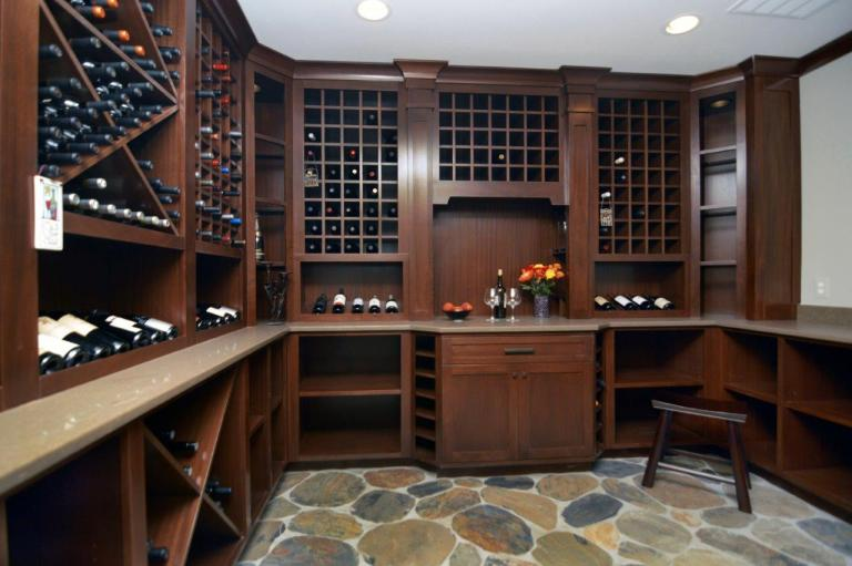 wine cellar with stone floors dark cabinetry plenty of wine storage recessed lighting