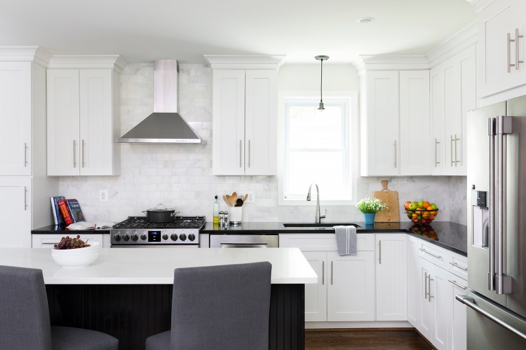 renovated kitchen with white cabinetry stainless steel appliances sink in front of window with pendant lighting above