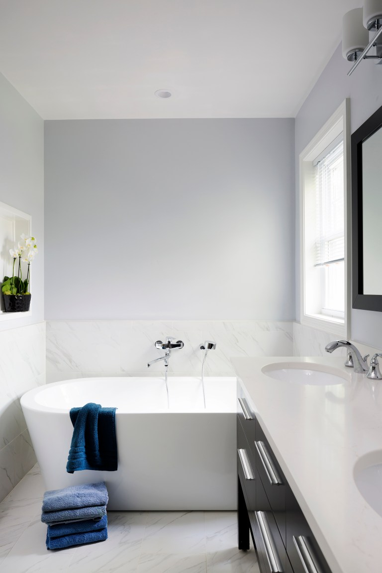 freestanding bathtub with wall mounted fixtures half wall tiling nook built into wall