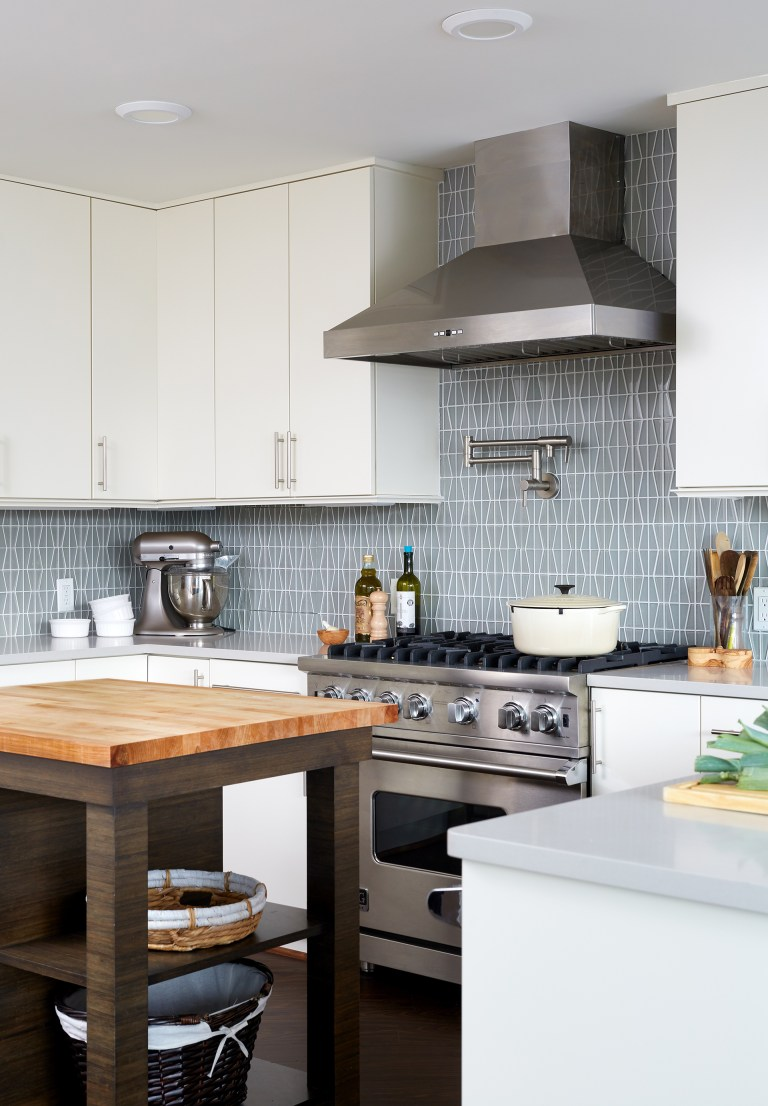 kitchen with white outer cabinets natural wood island geometric backsplash stainless steel gas range and hood