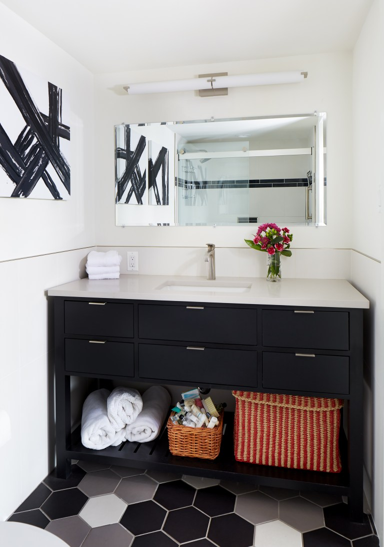 bathroom with black gray and white color scheme vanity with open shelving underneath