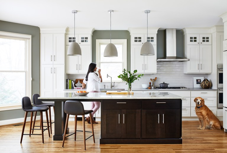 kitchen with wood floors white outer cabinets and dark stained island with seating pendant lighting