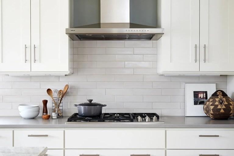 gas stovetop and stainless steel range hood white subway tile backsplash